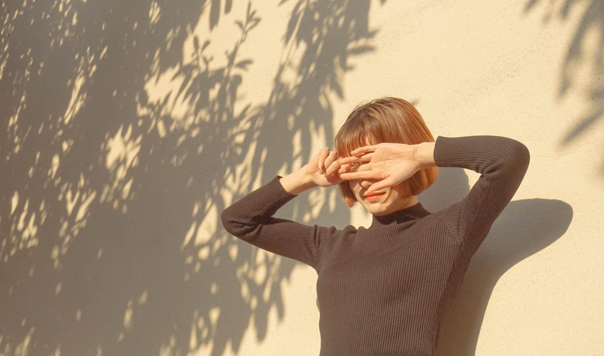 Fotografía de mujer tapándose la cara por reflejo del sol